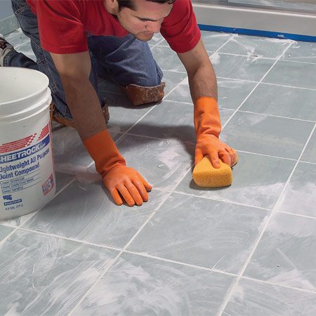 <b>Photo 17: Clean the tiles</b></br> Wipe grout off the tile surface with a damp sponge. Wipe gently on the first pass so you don't pull grout out of the joints. Rinse the sponge often.