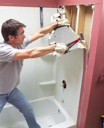 <b>Photo 3a: Pull the drywall and tub surround from the studs</b></br> Pull off the drywall with a hammer and pry bar, working from the edges. Keep an eye out for wires and pipes. Wear safety glasses!