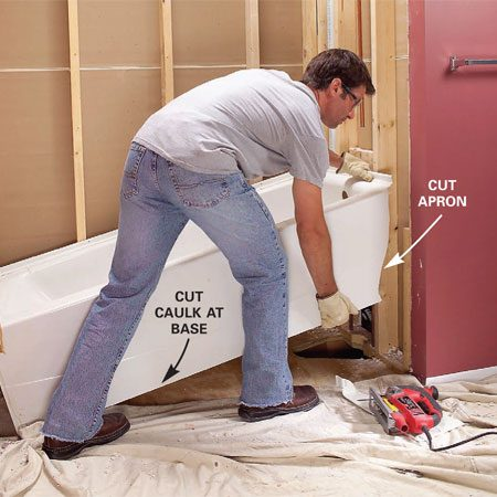 <b>Photo 5: Lift one end and remove the tub</b></br> Cut the apron at one end (plastic tubs) with a jigsaw, slice the caulk along the floor, remove any fasteners, and lift the tub up and out.