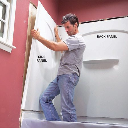 <b>Photo 9: Set the back panel first</b></br> Set the back surround panel into place and then set the side panels. Chisel off protruding studs and trim the drywall as necessary to get a good fit.