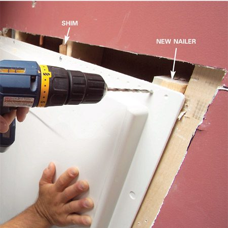 <b>Photo 11: Fasten the panels</b></br> Set the panels and interlock them with the tub and adjust them until the tops are even. Then predrill and fasten the flanges at each stud. Add shims to fill gaps and keep the flange straight.