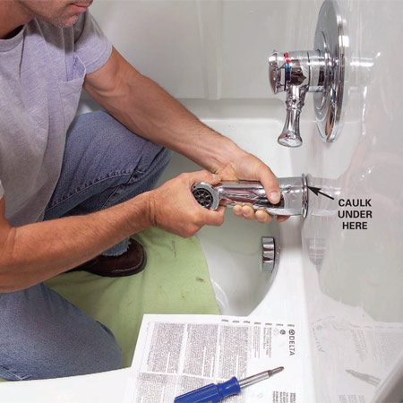 <b>Photo 14: Fit the faucet trim</b></br> Attach the cover plate and valve handle. Add caulk and snug the spout into place