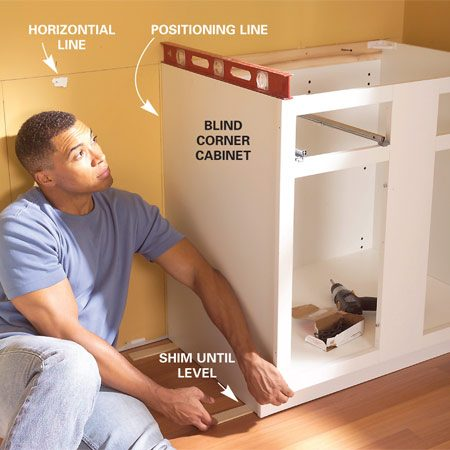 <b>Photo 2: Position the first cabinet</b></br> Set the first cabinet 1/4 in. from the positioning line and shim the base until the top is even with the horizontal line and level from front to back. Drive 2-1/2-in. screws through the back into the wall studs to anchor it.