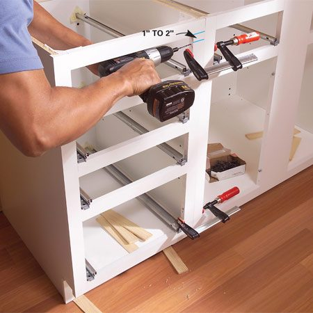 <b>Photo 3: Screw face frames together</b></br> Shim the next cabinet even with the horizontal line and level it. Clamp the frames together, drill 1/8-in. pilot holes, and screw the frames together with 2-1/2- in. screws. Then screw the cabinet to the wall studs.
