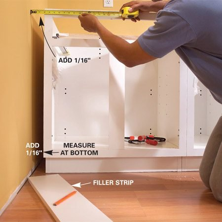 <b>Photo 4: Measure the gap</b></br> Measure the gap between the wall and the end cabinets at the top and bottom. Add 1/16 in. to each measurement and draw a cutting line on the backside of a filler strip.
