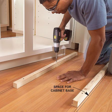 <b>Photo 10: Install 2 x 2 support</b></br> Draw a second line to mark the thickness of the cabinet base, then screw 2x2s to the floor along the inner line.