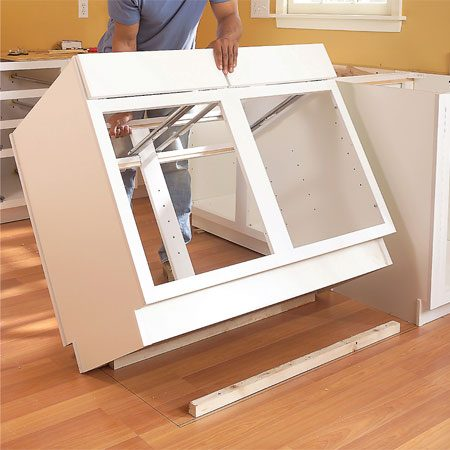 <b>Photo 11: Set the cabinet</b></br> Lower the cabinet over the blocking. Shim, clamp and screw the frames together. Screw the cabinet to the blocking with two screws from each side.