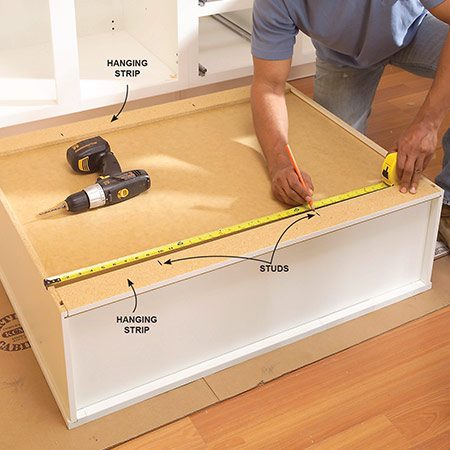<b>Photo 13: Mark stud locations</b></br> Measure from the cabinet position lines to the stud locations. Mark the stud locations on the cabinet backs and drill 1/8-in. pilot holes through the hanging strips.
