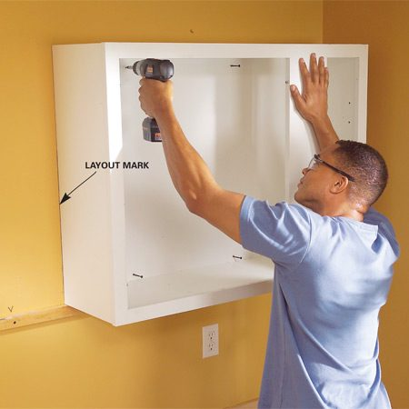 <b>Photo 14: Screw the cabinets to the wall</b></br> Start 2-1/2-in. screws, then rest the cabinet on the ledger. Align it with the cabinet position line and drive the screws into the wall studs.