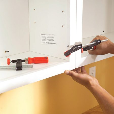 <b>Photo 15: Hang additional cabinets</b></br> Position the next cabinet and run the top screws partially into the studs to hold it in place. Align the frames, clamp them and screw the cabinets together. Then screw the cabinet to the wall.