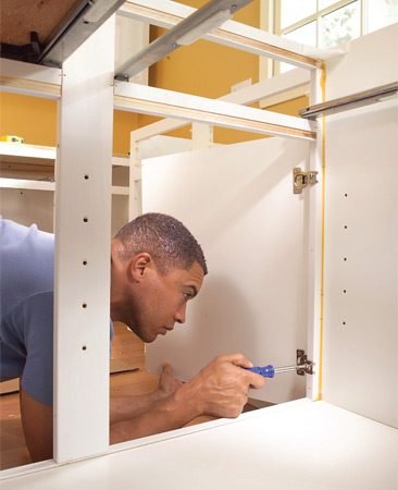<b>Photo 16: Install cabinet doors</b></br> Replace the drawers, then rehang the doors and adjust the hinges to align the doors with one another.