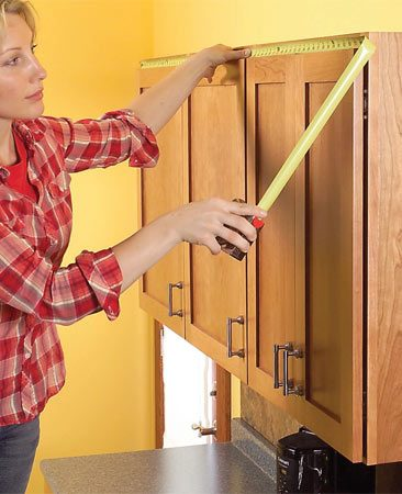 <b>Photo 1: Measure for materials</b></br> Measure the tops of your cabinets to determine your materials list. Also check the distance above the cabinet doors to determine the support cleat height for the shelf.