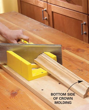<b>Photo 7: Cut the crown</b></br> Position your molding upside down in the miter box to support both the top and the bottom of the molding. Check the direction of the angle twice before you cut.