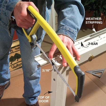 <b>Photo 3: Fasten the hinge-side Z-bar</b></br> Confirm the door swing direction and fasten the hinge-side Z-bar to the correct side (if necessary). Mark a cutting line on the Z-bar 3/16 in. above the top of the door with a square. Slide the weatherstripping aside and cut the Z-bar with a hacksaw. Use an 18- to 22-tooth-per-in. hacksaw blade