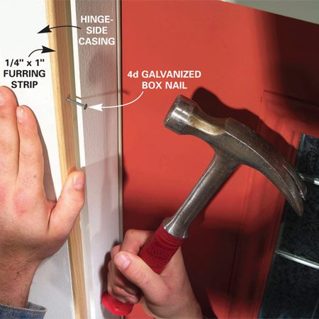 <b>Photo 6: Add a furring strip</b></br> Measure the opening width and determine the furring strip thickness (see text). Cut a furring strip to length, then nail it to the inside edge of the hinge-side casing with four evenly spaced 4d galvanized box nails.