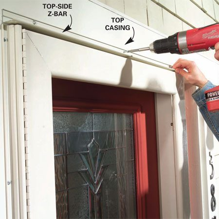 <b>Photo 8: Install the top Z-bar</b></br> Swing the door open, slip the top-side Z-bar into place and close the door to hold it. Adjust the gap between the Z-bar and the top of the door until it's even and screw it into the top casing.