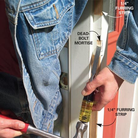 <b>Photo 11: Chisel the dead bolt mortise</b></br> Close the door against the casing with the dead bolt extended and chisel out the wood where the deadbolt hits. Slip the latchside Z-bar into place, close the door against it and screw it to the casing, keeping a consistent 1/8-in. gap with the door.