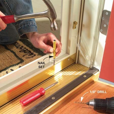 <b>Photo 12: Adjust the door sweep</b></br> Slide the rubber weatherstripping into the door sweep and crimp the ends. Slide the sweep over the door bottom and tap it down to snug it to the threshold. Drill 1/8-in. holes through the adjustment slots and add the screws.