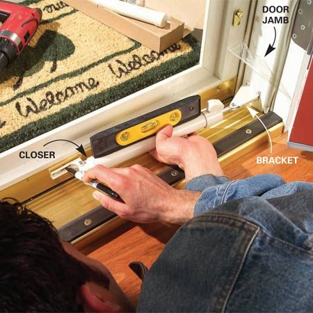 <b>Photo 13: Attach closers</b></br> Position the closer bracket and screw it to the jamb. Attach the closer, level it and mark the screw positions on the door. Drill 1/8-in. pilot holes and screw the closer to the door. Repeat for the top closer.