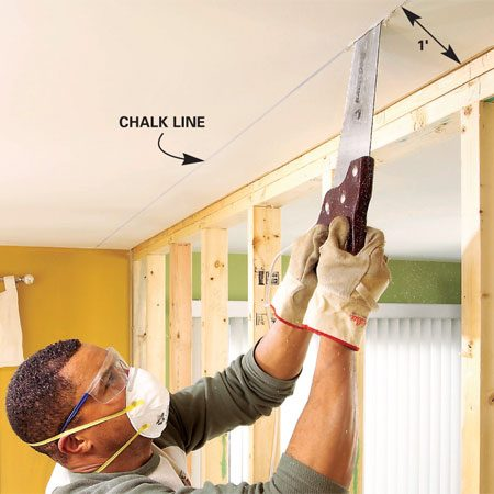 <b>Photo 2: Cut a slot in the ceiling </b></br> <p>Snap a chalk line about 12 in. out from the wall and cut a slot. Strip 1 ft. of ceiling drywall from one side of the wall. (Use shallow strokes to avoid nicking any electrical cables hidden in the ceiling.)</p>