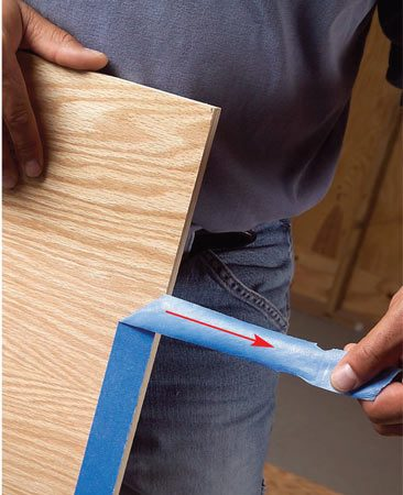 <b>Photo 2: Pull tape carefully</b></br> Remove the tape by pulling it at a 90-degree angle away from the cut edge. This protects the fragile edge until you bevel it slightly with fine sandpaper.