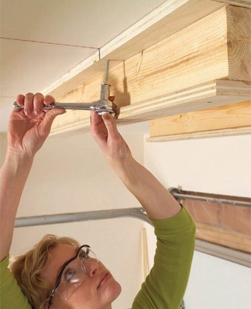 <b>Photo 8: Drive lags at joists</b></br> Drill 3/16-in. pilot holes in the top flanges. Then drive pairs of 3-1/2-in. lag screws into each joist, removing the temporary screws as you go. Use a minimum of four lag screws per carriage.