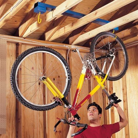 <b>Build a moveable rack</b></br> Build this moveable bike rack from a 2x4 and a pair of bicycle hooks. Cut four 3-1/2-in. blocks, stack two on top of each other, and screw them together. Now screw them on the end of a 4-ft. 2x4 and repeat the process for the other side. Drill a hole in the middle of the stacked blocks and screw in the bicycle hooks. Lay the rack across your garage ceiling joists, and hang your bike from the hooks. When you need to get behind the bike, simply slide the entire rack out of the way.