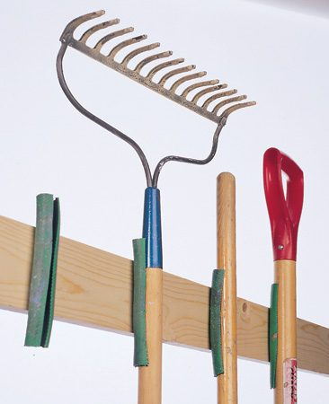 <b>Nail hose pieces to the wall</b></br> Cut an old hose into 7-in. pieces, slit them, and nail them to the wall to make good holders for handled tools in the garage.