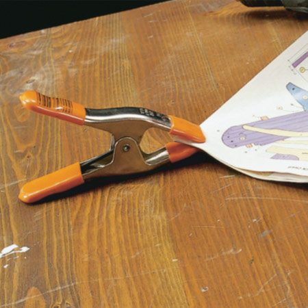 <b>Spring clamp keeps pages in place</b></br> To solve that problem, put spring clamps at the corners of the plans or magazine to keep it on the table and open to the desired page.