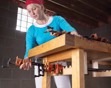 <b>Rack attaches under your workbench</b></br> This handy under-mount rack keeps your clamps right where you need them. Simply cut a series of 1-1/4-in.-diameter holes along the center line of a 2x6 and then rip the 2x6 in half to create the half-circle slots.
