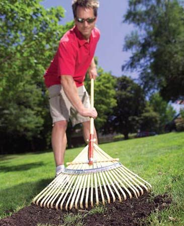 <b>Photo 3: Rake in topsoil</b></br> Spread 1/4 in. of topsoil on the yard's most thatchy areas and then rake vigorously to fill the holes with loose soil.
