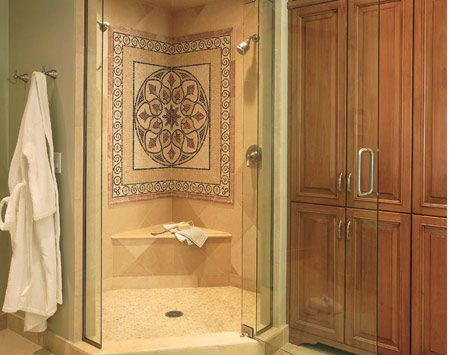 <b>A beautiful shower stall mosaic.</b></br> A spacious corner shower—complete with tile medallion—includes a fixed shower head on the right and an adjustable handset on the left.