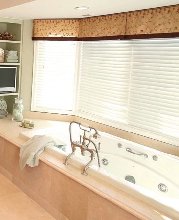 <b><p>The finished whirlpool bath enclosure with a limestone deck and tile</p></b></br> An oversize whirlpool tub sits beneath the bay window.