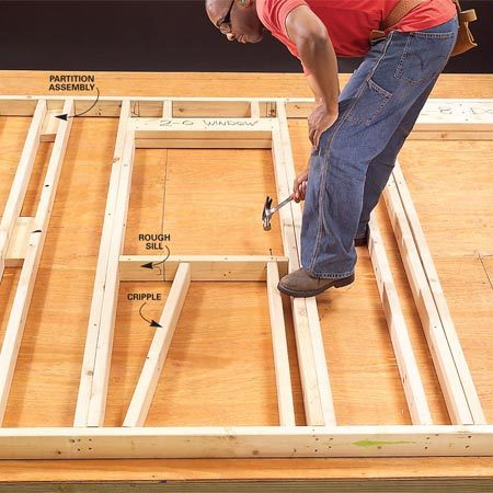 <b>Add sills for windows</b></br> Window openings are just like doors but with the addition of a rough sill. Mark the top of the sill by measuring down from the header. Use the rough opening height for this dimension. Cut the lower cripples and place one under each end of the sill as a temporary support while you toenail the sill to the trimmers with a pair of 8d nails at each end. Align the cripples with the layout marks and nail through the sill and bottom plate to hold them in place. Use pairs of 16d nails. Some carpenters like to double the rough sill, especially on openings wider than about 3 ft. If you do this, remember to allow for the thickness of a double sill when you cut your cripples.