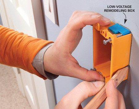 <b>Photo 1: Cut the hole for the low-voltage box</b></br> Choose a location for the keypad and trace around the box, making sure to mark the notches for the clips. Probe for obstructions with a stiff wire, then cut along the lines with a drywall keyhole saw.