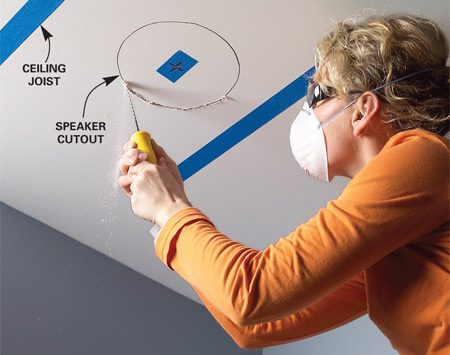 <b>Photo 2: Cut the holes for the speakers</b></br> Mark both speaker locations with masking tape and probe for obstructions. Trace around the template and cut out the opening with a drywall saw.