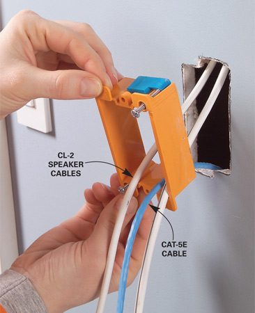 <b>Photo 5: Pull the wire through the box </b></br> Slide the low-voltage remodeling box into the wall and tighten the screws until the clips are snug to the drywall.