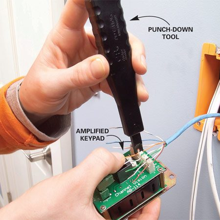 <b>Photo 7: Match the wires to the keypad </b></br> Lay each wire into its corresponding groove on the back of the amplified keypad and punch them down with the punch-down tool. Trim the ends of the wires with a scissors or end cutter.