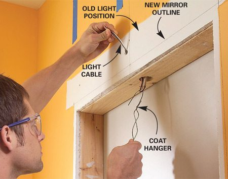 <b>Photo 4: Pull the light </b></br> Outline the new mirror position using a level. Drill a 1-1/2-in. hole in the top framing and pull the power cable down into the opening.