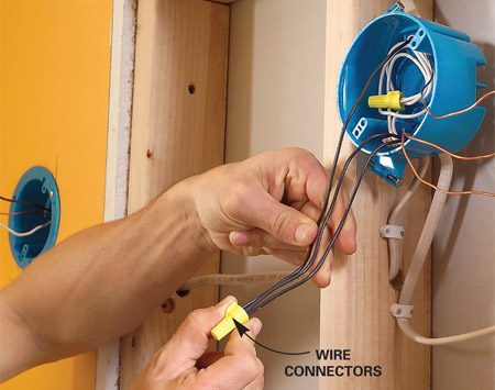 <b>Photo 8: Carefully check wiring details </b></br> Join the black (hot) wires, the white (neutral) and the ground wires. Cap the exposed sconce wires with connectors and tuck the wires into the boxes.