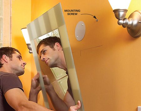 <b>Photo 12: Hang the mirror</b></br> Hang the mirror, adjusting the screw heads in or out until the mirror hangs snugly against the wall.