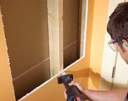 <b>Photo 2: Cut the opening</b></br> Cut the intermediate stud flush with the drywall on the backside. Push it sideways to release the drywall screws on the backside and remove the stud.