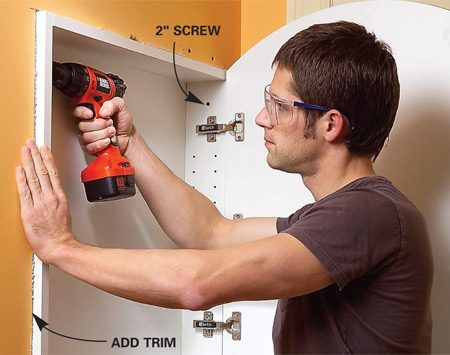 <b>Photo 5: Install the medicine cabinet</b></br> Slip the cabinet into the opening and anchor it with pairs of 2-in. screws. Add trim if needed.