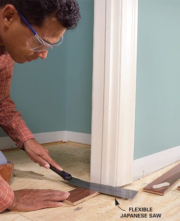 <b>Photo 1: Prepare the trim and base</b></br> Remove the baseboard. Undercut the bottoms of the doorjambs and casing so the flooring can slide under them. Place a piece of flooring under a flexible trim saw and carefully cut the trim.