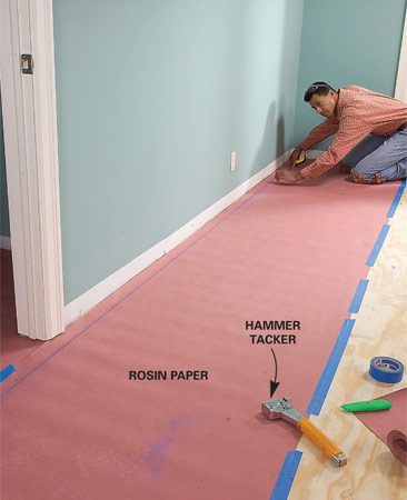 <b>Photo 2: Lay rosin paper</b></br> Tape and staple rosin paper to the subfloor. If your manufacturer prefers 15-lb. felt, use that instead. Snap a line 1/2 in. plus the width of the flooring from the straightest wall in the room.