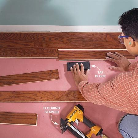<b>Photo 4: Tap the next rows in</b></br> Tap the second and third rows into place, making sure the ends and the sides fit snugly. Power-staple through the tongues every 6 in. Avoid placing joints of adjoining rows closer than 4 in., and place the joints as randomly as possible by choosing varying lengths of flooring.