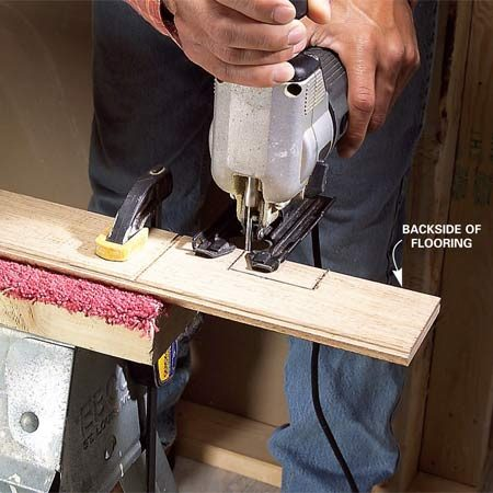 <b>Photo 6: Cut on the bottom side</b></br> Cut the flooring from the back side with a fine-tooth blade to avoid splintering. A jigsaw works well, especially for intricate cuts in doorways or around floor vents. Use a small table saw to rip pieces that lie against the end wall. Cut in another room to avoid dust.