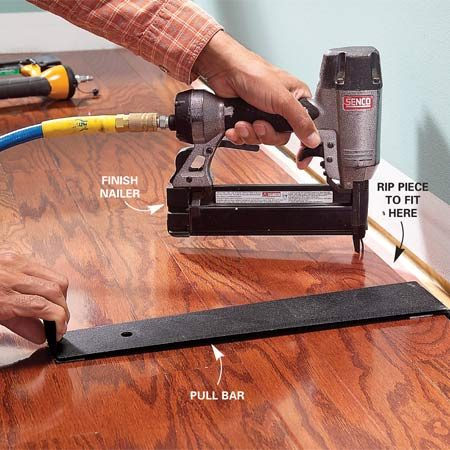 <b>Photo 8: Face-nail the last pieces</b></br> Tighten the flooring seams near the end wall with a pull bar, then face-nail the pieces about 1/2 in. back from the tongue. The stapler won't fit into this tight space.