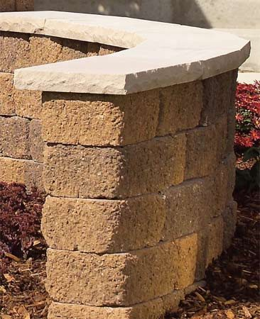 "<b>Strategy 6: Erect stone entry walls</b></br> Low stone walls are striking features that can define your entry and guide visitors up the walk. Natural stone is ideal but difficult to set. The decorative concrete units shown here are relatively inexpensive and easy to install. They subtly separate seating areas from public sidewalks and streets. And they're also great places for casual seating and potted plants. See ""Stone Wall,"" below, to see how to build one yourself."