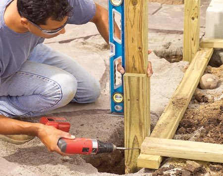 <b>Photo 3: Set the posts</b></br> Drop the posts into their postholes, then plumb them both ways and toe-screw them to the template. Tamp soil around it to brace it.